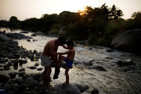 A migrant from Honduras helps his child get dressed after a bath in a river during a break in his journey towards the United States, in Huixtla, Mexico April 16, 2019. REUTERS/Jose Cabezas