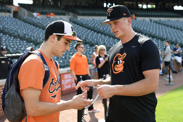 Baltimore Orioles first-round draft pick Adley Rutschman, right, signs for fans during batting practice before a baseball game against the San Diego Padres, Tuesday, June 25, 2019, in Baltimore. (AP Photo/Nick Wass)