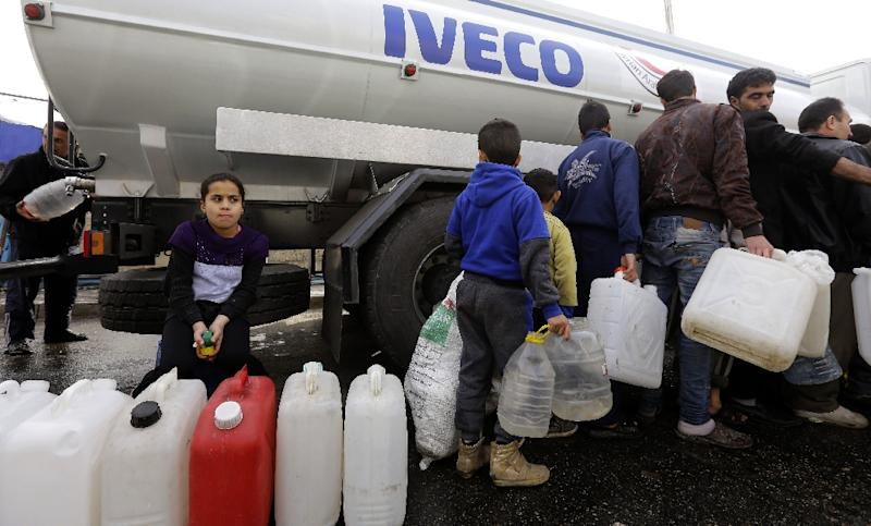 Syrians wait to fill plastic containers with water provided by the Syrian Arab Red Crescent in the capital Damascus on January 10, 2017 (AFP Photo/LOUAI BESHARA)
