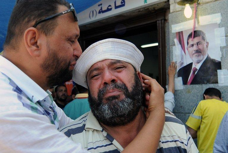 A man at the Muslim Brotherhood field hospital in Cairo on Saturday mourns the death of a relative in clashes overnight. Dozens of Mohamed Morsi's supporters were shot dead in the Egyptian capital on Saturday as violence erupted after a night of massive rallies for and against the ousted Islamist president