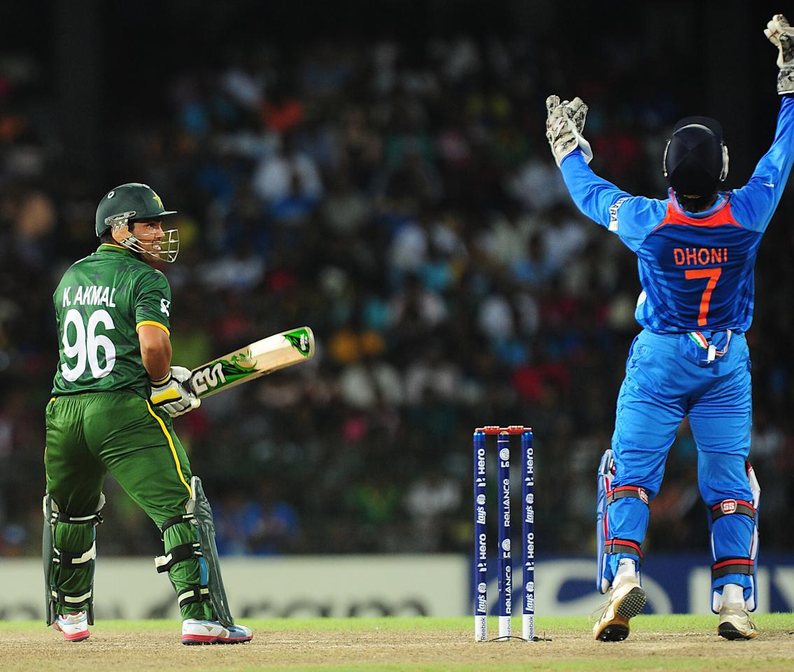 Pakistan batsman Kamran Akmal (L) watches as Indian captain and wicketkeeper Mahendra Singh Dhoni (R) takes a catch to dismiss him during the ICC Twenty20 Cricket World Cup's Super Eight match between India and Pakistan at The R. Premadasa International Cricket Stadium in Colombo on September 30, 2012. AFP PHOTO/ LAKRUWAN WANNIARACHCHI