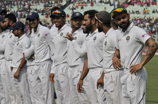 Indian cricket captain Virat Kohli, right, stands with teammates during the first day of the second test match against Bangladesh in Kolkata, India, Friday, Nov. 22, 2019. India and Bangladesh are playing their first day-night test match with a pink ball. (AP Photo/Bikas Das)