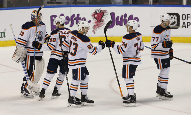 Edmonton Oilers players celebrate their 4-2 win over the Florida Panthers in an NHL hockey game, Saturday, March 17, 2018, in Sunrise, Fla. (AP Photo/Joe Skipper)