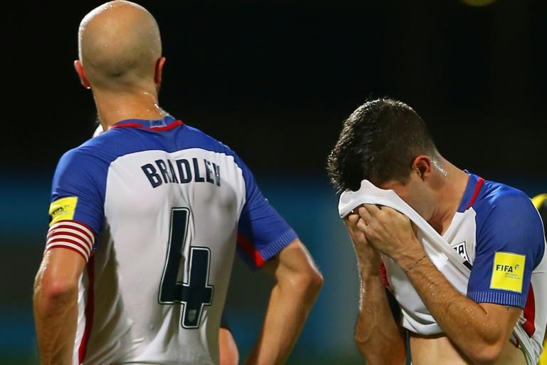 Michael Bradley (L) and Christian Pulisic of the US react to loss against Trinidad and Tobago after their FIFA 2018 World Cup qualifier match, at the Ato Boldon Stadium in Couva, Trinidad And Tobago, on October 10, 2017