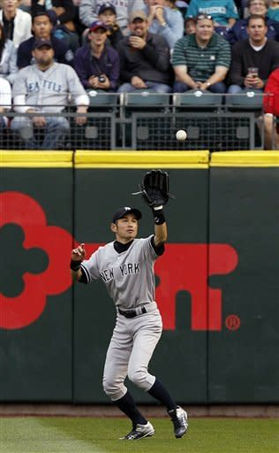 New York Yankees right fielder Ichiro Suzuki catches a fly ball from Seattle Mariners' Kyle Seager in the first inning of a baseball game Monday, July 23, 2012, in Seattle. (AP Photo/Elaine Thompson)