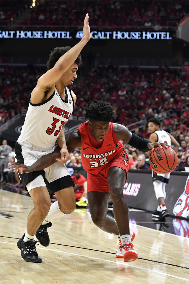 Youngstown State guard Garrett Covington (32) attempts to drive past the defense of Louisville forward Jordan Nwora (33) during the first half of an NCAA college basketball game in Louisville, Ky., Sunday, Nov. 10, 2019. (AP Photo/Timothy D. Easley)