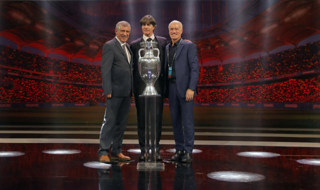 The coaches of Portugal Fernando Santos, left, Germany Joachim Loew and France Didier Deschamps who will play in group F, pose with the trophy after the draw for the UEFA Euro 2020 soccer tournament finals in Bucharest, Romania, Saturday, Nov. 30, 2019. (AP Photo/Vadim Ghirda)