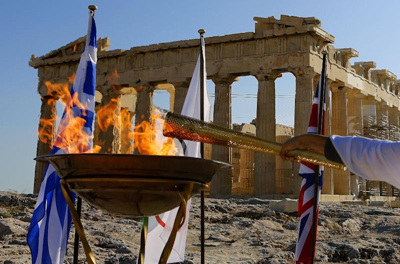 Torchbearer Dimitrios Chondrokoukis, a Greek high jump athlete, lights a cauldron with the Olympic Flame atop the Athens Acropolis Wednesday May 16, 2012. The Olympic flame will be handed over to the London 2012 delegation on Thursday. (AP Photo/Yannis Behrakis/pool)