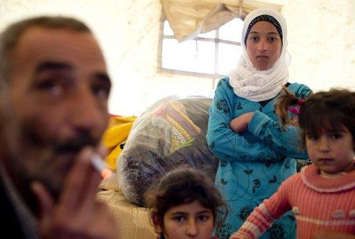 A Syrian refugee family gathers inside a tent after arriving to the Turkish side of the Orontes river after fleeing from the northern Syrian town of Darkush on December 13, 2012. The number of Syrian refugees registered in neighbouring countries and North Africa has passed half a million, the UN's refugee body said, adding that many more have not come forward to seek help. AFP PHOTO / ODD ANDERSEN (AFP | Odd Andersen)
