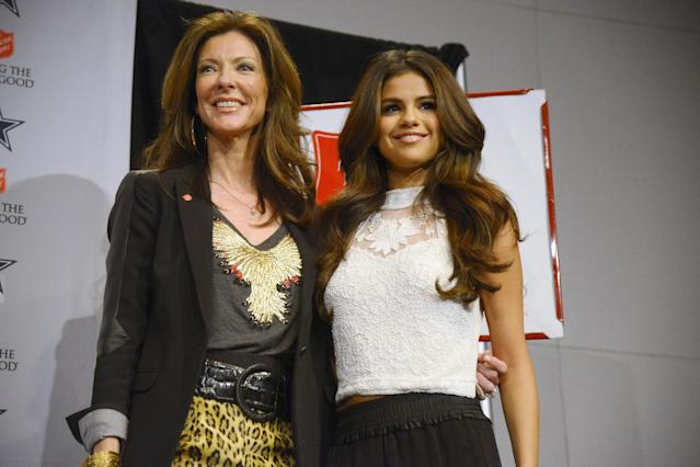 Dallas Cowboys Executive Vice President and Chief Brand Officer Charlotte Anderson poses with entertainer Selena Gomez, right, during a news conference before an NFL football game against the Minnesota Vikings, Sunday, Nov. 3, 2013, in Arlington, Texas. Gomez will be the half time entertainment on Thanksgiving when the Cowboys take on the Oakland Raiders. (AP Photo/Tim Sharp)