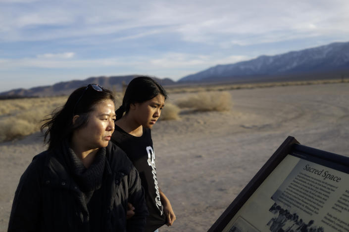 Lori Matsumura, left, and her niece, Lilah Matsumura, view a sign at Manzanar National Historic Site near Independence, Calif., Monday, Feb. 17, 2020. The sign mentions that Lori Matsumura's grandfather, Giichi Matsumura, a prisoner at the internment camp, died while exploring the nearby high Sierra in 1945. Hikers discovered his mountainside grave and unearthed the skeleton in 2019, leading authorities to retrieve the bones and return them to the Matsumura family. (AP Photo/Brian Melley)