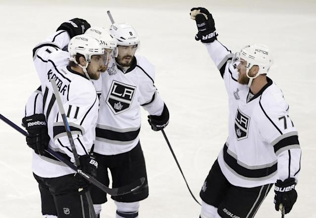 Los Angeles Kings center Anze Kopitar (11), left, and teammates Drew Doughty (8), third from left, and Jeff Carter (77), right, celebrate a second period goal by defenseman Jake Muzzin (6), second from left, against the New York Rangers during Game 3 of the NHL hockey Stanley Cup Final, Monday, June 9, 2014, in New York. (AP Photo/Frank Franklin II)
