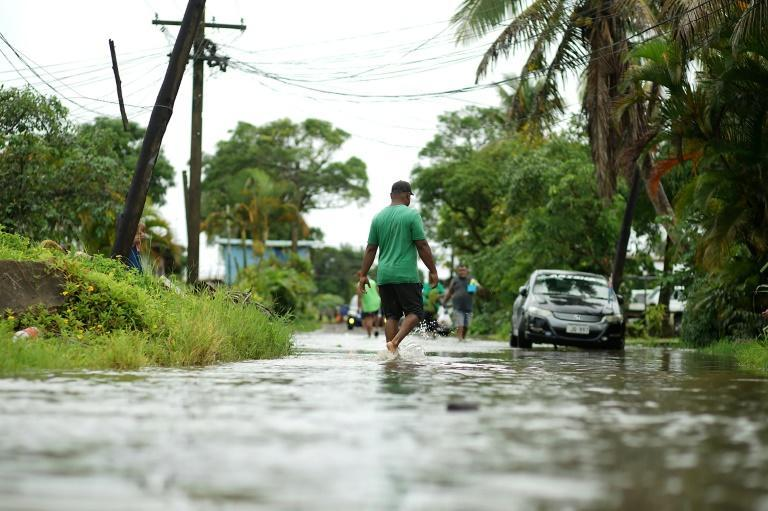 Residents wade through the flooded streets in Fiji's capital city of Suva ahead of super Cyclone Yasa