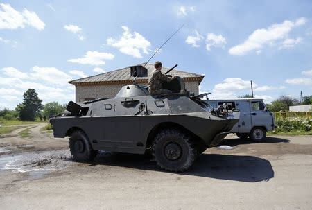 A pro-Russian separatist drives an armoured vehicle in Seversk (Siversk), located near the town of Krasny Liman, Donetsk region, June 19, 2014. REUTERS/Shamil Zhumatov