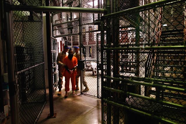 """GUANTANAMO BAY, CUBA - OCTOBER 27: (EDITORS NOTE: Image has been reviewed by U.S. Military prior to transmission.) A """"non-compliant"""" detainee is escorted by guards after showering inside the U.S. military prison for """"enemy combatants"""" on October 27, 2009 in Guantanamo Bay, Cuba. Although U.S. President Barack Obama pledged in his first executive order last January to close the infamous prison within a year's time, the government has been struggling to try the accused terrorists and to transfer them out ahead of the deadline. Military officials at the prison point to improved living standards and state of the art medical treatment available to detainees, but the facility's international reputation remains tied to """"enhanced interrogation techniques"""" such as waterboarding employed under the Bush administration. (Photo by John Moore/Getty Images)"""