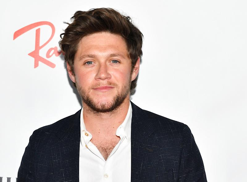 Niall Horan looks amazing in a well tailored dark blue suit with white inner T-shirt.