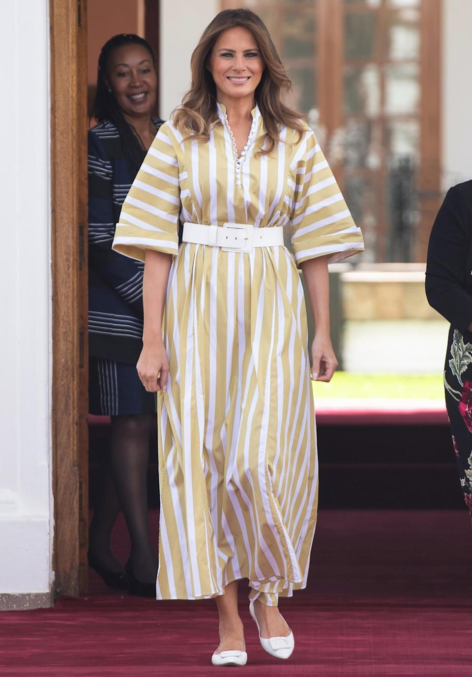 Wearing a muted yellow and white striped dress with a matching belt and flats, the First Lady covered up while meeting with teh First Lady of Kenya, Margaret Kenyatta. [Photo: Getty]