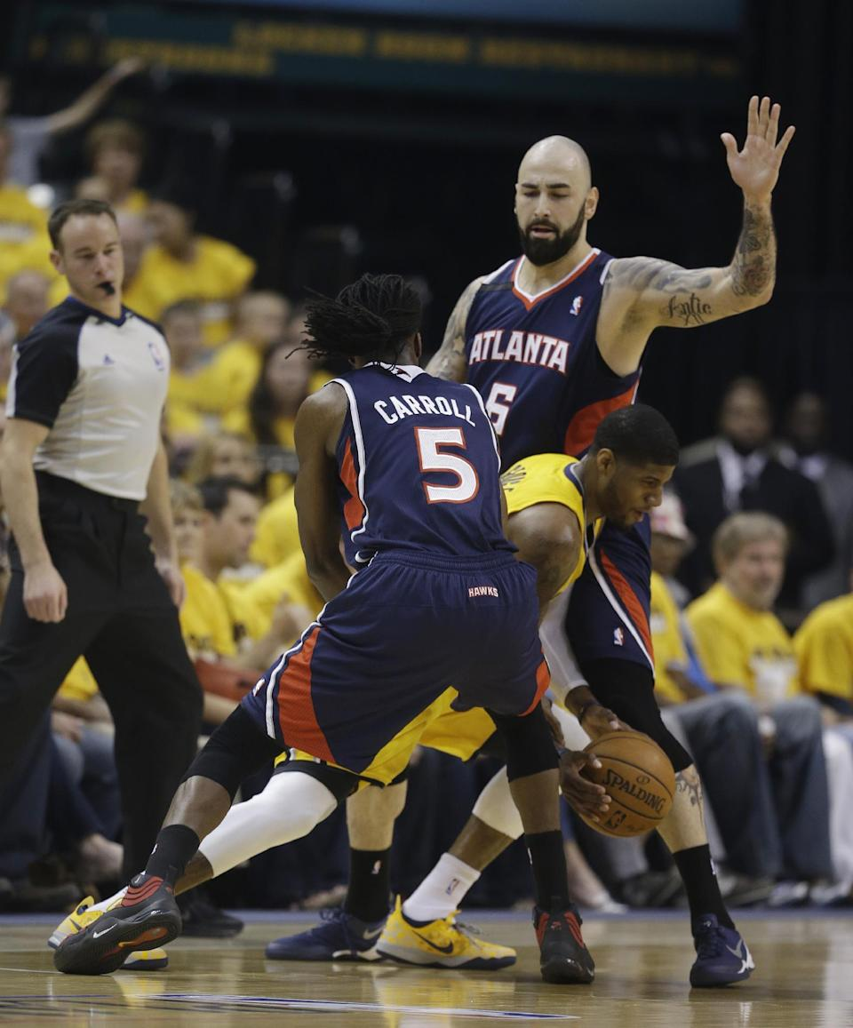 Indiana Pacers' Paul George, center, is defended by Atlanta Hawks' DeMarre Carroll (5) and Pero Antic (6) during the first half in Game 1 of an opening-round NBA basketball playoff series Saturday, April 19, 2014, in Indianapolis. (AP Photo/Darron Cummings)