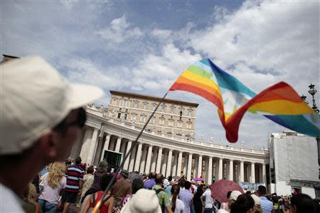 A man waves a peace flag as Pope Francis leads his Sunday angelus prayer in Saint Peter's Square at the Vatican