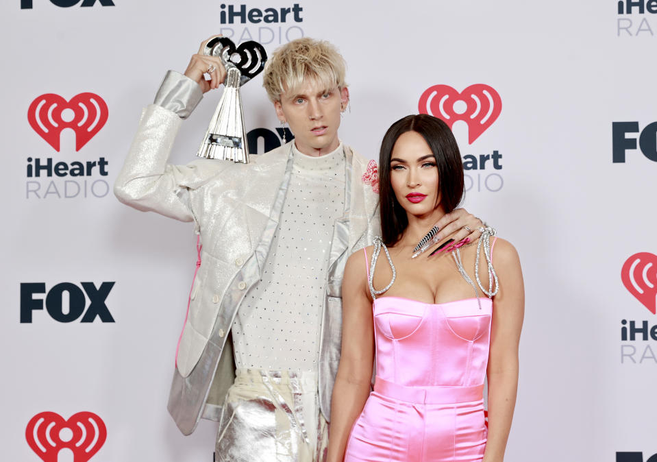 LOS ANGELES, CALIFORNIA - MAY 27: (EDITORIAL USE ONLY) (L-R) Machine Gun Kelly, winner of the Alternative Rock Album of the Year award for 'Tickets To My Downfall,' and Megan Fox attend the 2021 iHeartRadio Music Awards at The Dolby Theatre in Los Angeles, California, which was broadcast live on FOX on May 27, 2021. (Photo by Emma McIntyre/Getty Images for iHeartMedia)