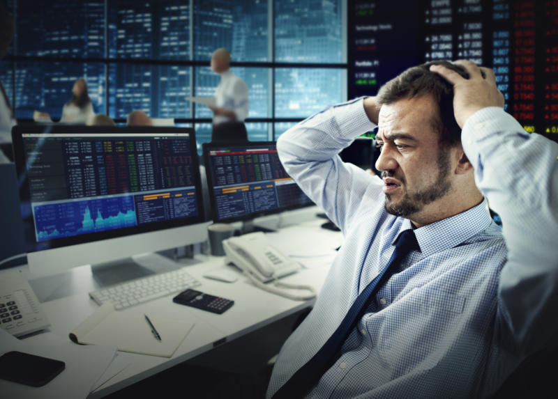 A visibly frustrated stock trader grasping the top of his head while looking at losses on his computer monitor.