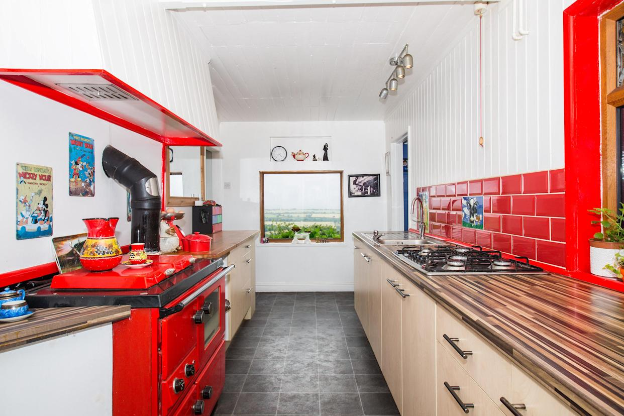 There's a lovely kitchen, which comes complete with picture window and red range. (SWNS)
