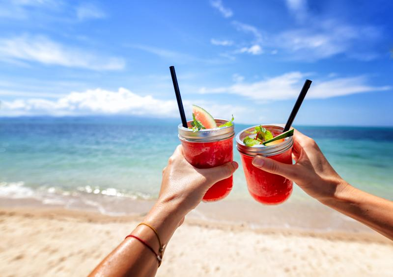 Fresh watermelon juice with a straw in two glasses against a bright tropical landscape, against the background of the sea. Vacation vacations healthy food concept