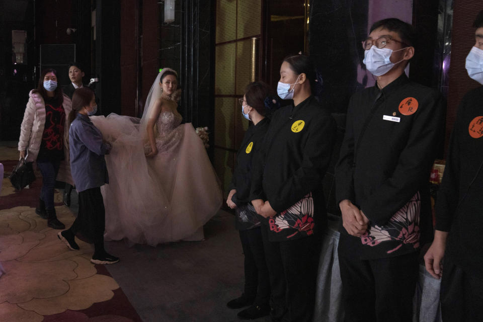 Bride Chen Yaxuan walks by staff wearing masks during a wedding banquet in Beijing on Saturday, Dec. 12, 2020. Lovebirds in China are embracing a sense of normalcy as the COVID pandemic appears to be under control in the country where it was first detected. (AP Photo/Ng Han Guan)