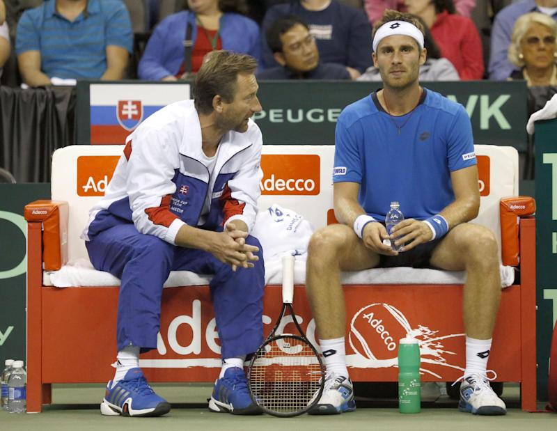 Slovakia Davis Cup Captain Miloslav Mecir, left, talks with Norbert Gombos, during a break in play of the first set of a Davis Cup World Group playoff match against John Isner, of the United States,  Friday, Sept. 12, 2014, at the Sears Centre Arena in Hoffman Estates, Ill. (AP Photo/Charles Rex Arbogast)