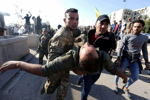 PHOTO: A wounded member of Hashd al-Shaabi (paramilitary forces) gets help during a protest to condemn air strikes on their bases, outside the main gate of the U.S. Embassy in Baghdad, Dec. 31, 2019. (Khalid Al-mousily/Reuters)