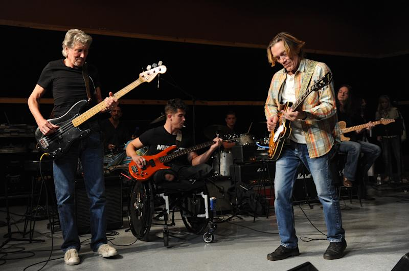 "Musician Roger Waters, left, and his band member guitarist G.E. Smith, right, hold rehearsals with members of the Wounded Warriors Project, including Marine Corporal Marcus Dandre, for the ""Stand Up For Heroes"" benefit concert presented by the New York Comedy Festival & the Bob Woodruff Foundation at S.I.R. Studios on Monday, Nov. 4, 2013, in New York. (Photo by Evan Agostini/Invision/AP)"