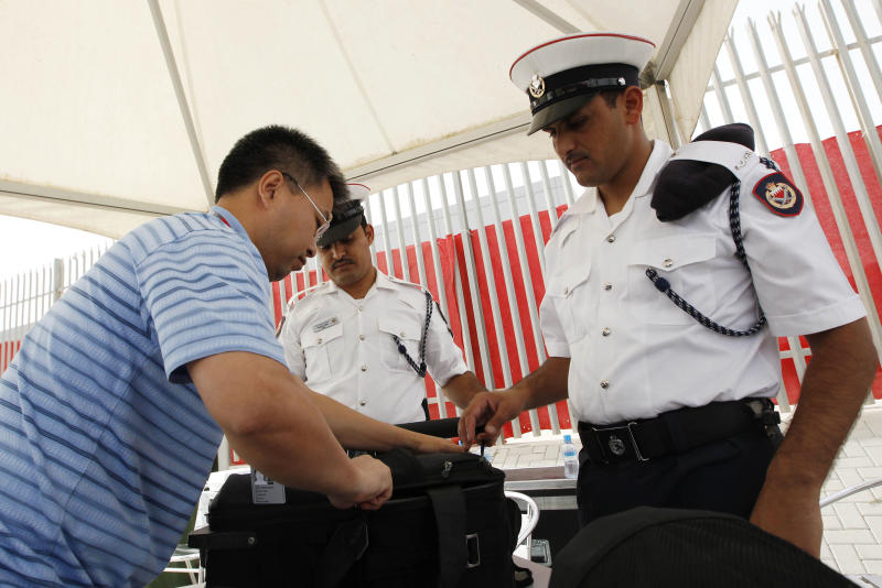Bahrain policemen check a reporter's bag and camera at a gate of the Formula One Bahrain International Circuit in Sakhir, Bahrain, Friday, April 20, 2012. Bahrain organizers hope to host the race this weekend despite protests and political unrest in the area. (AP Photo/Luca Bruno)