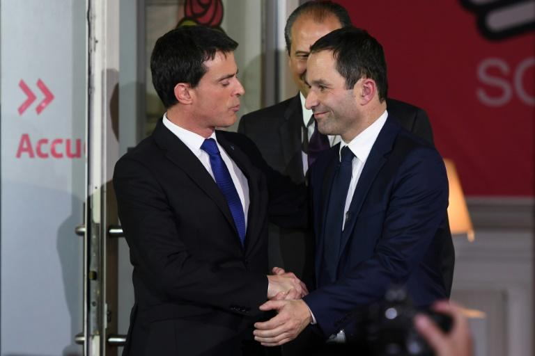 Benoit Hamon (R) shakes hands with defeated candidate Manuel Valls (L) next to French Socialist Party leader Jean-Christophe Cambadelis (C) following the announcement of the results of the second round of the left primaries on January 29, 2017
