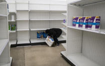 Deanna Butts reaches for one of the last packages of toilet paper at Target in the Tenleytown area of Washington, Tuesday, March 17, 2020. Supplies are restocked as trucks come in but the coronavirus outbreak is causing a current shortage of some items. (AP Photo/Carolyn Kaster)