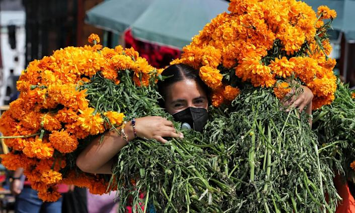 A woman transports cempasuchil (marigold) flowers ahead of Day of the Dead celebrations in Mexico City.