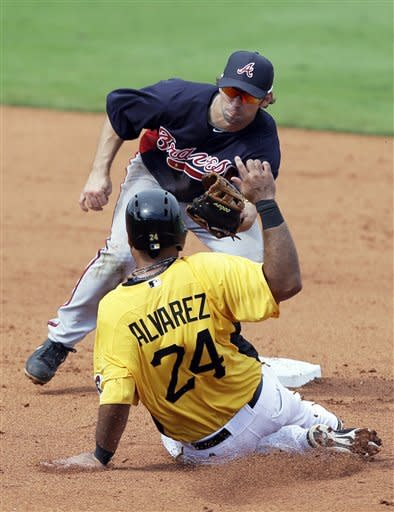 Pittsburgh Pirates' Pedro Alvarez (24) slides before being tagged out by Atlanta Braves second baseman Blake DeWitt, top, while trying to steal second base during the fourth inning of a baseball spring training game, Sunday, Feb. 24, 2013, in Bradenton, Fla. (AP Photo/Charlie Neibergall)