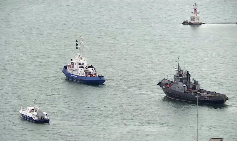 This video grab provided by the Krym 24 tv station via AP Television shows a seized Ukrainian ship, right, is towed by a Russian coast guard boat out of the port in Kerch, Crimea, Sunday, Nov. 17, 2019. Russia's Foreign Ministry says three Ukrainian naval ships that were seized in a shooting confrontation nearly a year ago have been returned. (Krym 24 tv station via AP Television)