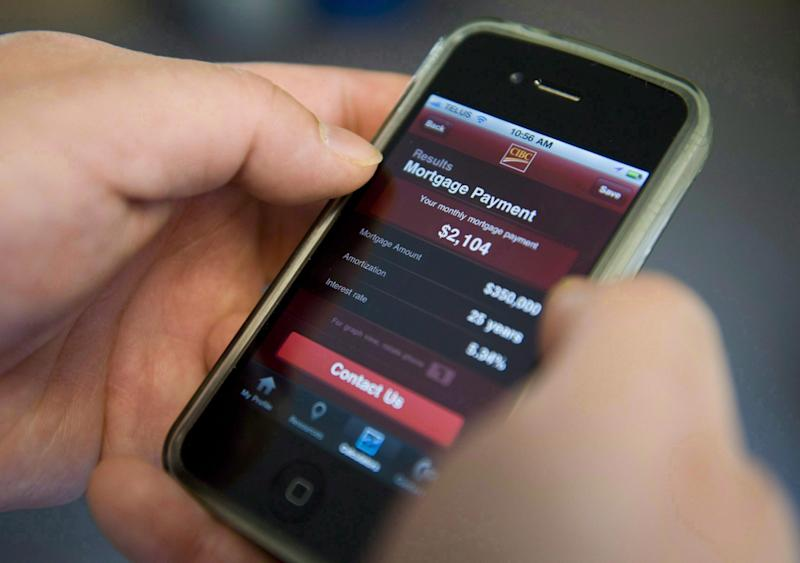 A smart phone user checks their bank account with an online banking app from CIBC in Ottawa on Friday, April 1, 2011. (THE CANADIAN PRESS/Sean Kilpatrick)
