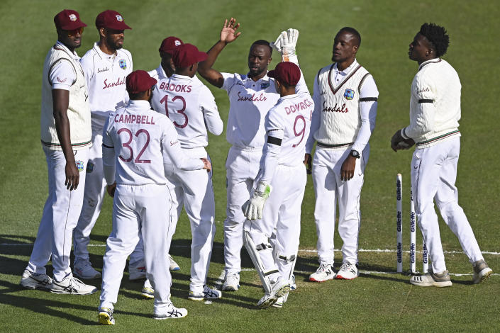 The West Indies Kemar Roach, centre, celebrates with his teammates after taking the wicket of New Zealand's Tom Latham during play on day one of the first cricket test against New Zealand in Hamilton, New Zealand, Thursday, Dec. 3, 2020. (Andrew Cornaga/Photosport via AP)