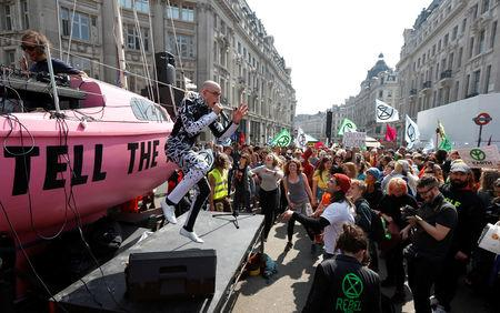 A performer sings to climate change activists demonstrating at Oxford Circus during an Extinction Rebellion protest in London, Britain April 15, 2019. REUTERS/Peter Nicholls