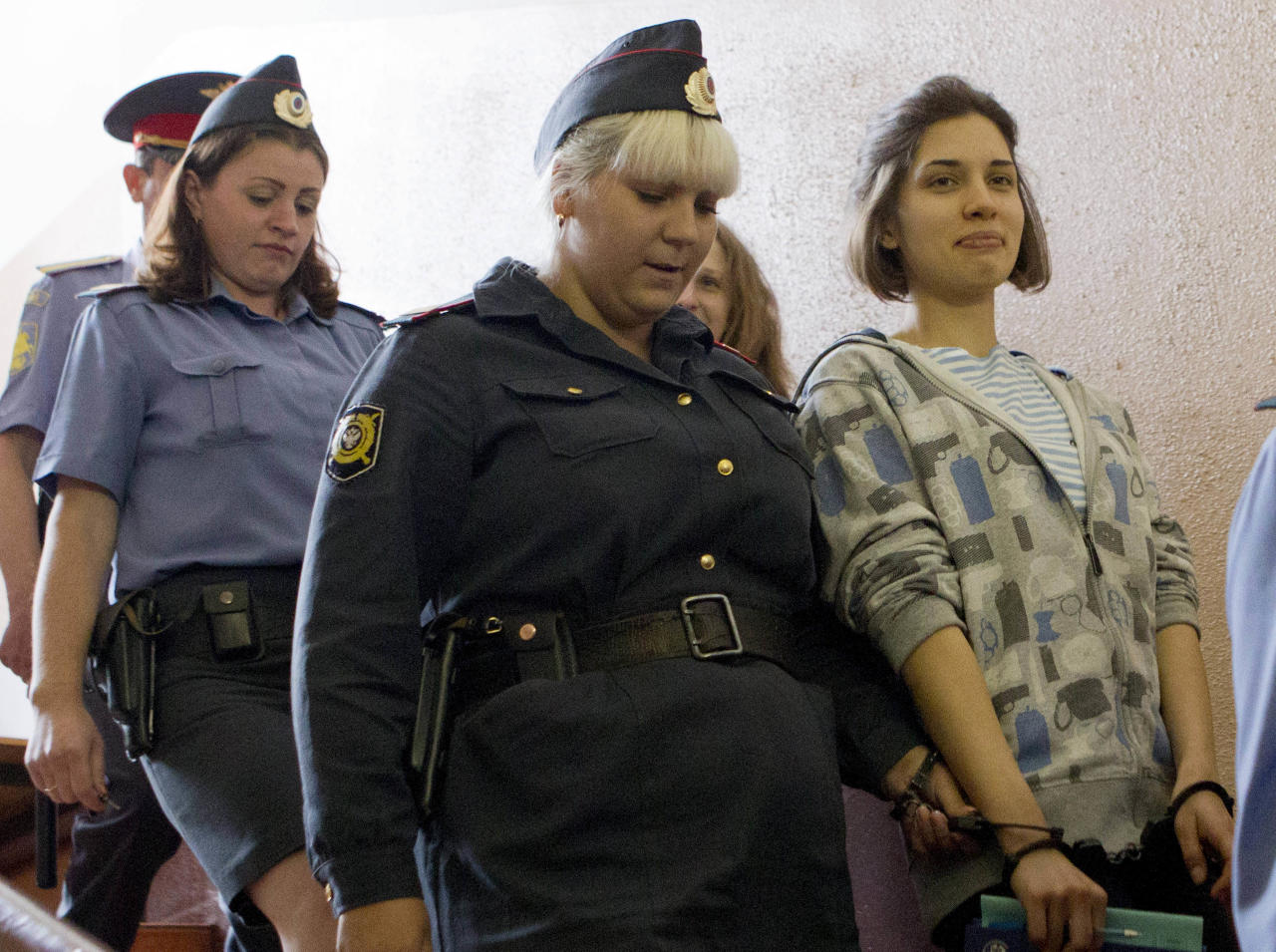 "Nadezhda Tolokonnikova, right, and Maria Alekhina, background center, members of feminist punk group Pussy Riot are excorted to a court room in Moscow, Russia, Friday, July 20, 2012. The trial of feminist punk rockers who chanted a ""punk prayer"" against President Vladimir Putin from a pulpit inside Russia's largest cathedral started in Moscow on Friday amid controversy over the prank that divided devout believers, Kremlin critics and ordinary Russians. (AP Photo/Misha Japaridze)"