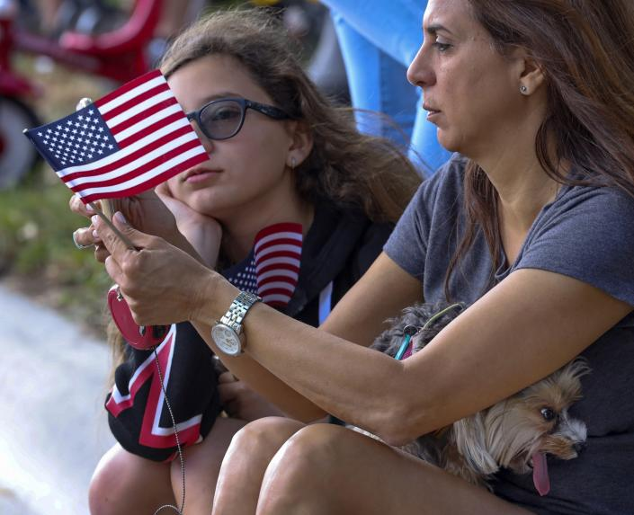 """Katia, 11, left, and mother, Cindy Rodriguez, 48, sits curbside watching the parade while their 3 year-old Yorkshire Terrier, """"Pixie', tries to keep cool during the city of Miami Lakes, Fla., Veterans Day Parade as veterans, Star Wars characters, cars, cheerleaders, school bands, flags, scouts, and others all paraded in honor veterans on Sunday, Nov. 10, 2019. (Photo: Carl Juste/Miami Herald via AP)"""