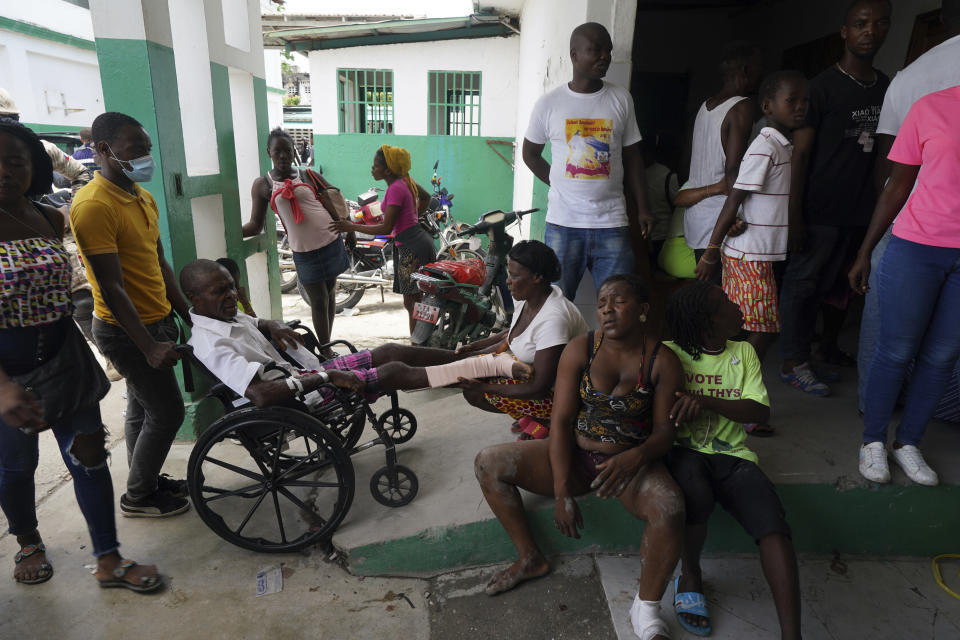 People injured in a car accident, sitting right, wait with others injured during the earthquake for x-rays at the General Hospital in Les Cayes, Haiti, Wednesday, Aug. 18, 2021. (AP Photo/Fernando Llano)