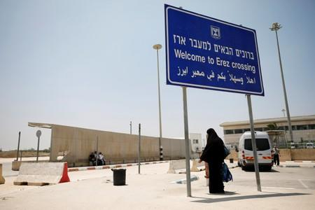 A Palestinian woman stands beneath a sign at the Israeli side of Erez crossing, on the border with Gaza