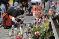 """People light candles at a growing memorial to victims of police violence, including George Floyd, Thursday, June 11, 2020, inside what is being called the """"Capitol Hill Autonomous Zone"""" in Seattle. Following days of violent confrontations with protesters, police in Seattle have largely withdrawn from the neighborhood, and protesters have created a festival-like scene that has President Donald Trump fuming. (AP Photo/Ted S. Warren)"""