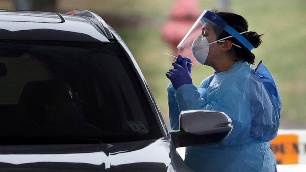 PHOTO: A medical staff member in protective gear administers a test for COVID-19 at a drive-through testing center in Paramus, N.J., March 20, 2020. (Seth Wenig/AP)