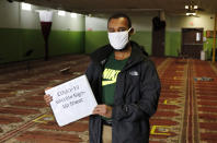 Abdiaziz Mohamed, who is in charge of coordinating vaccines for the Maine Muslim Community Center poses Wednesday, April 7, 2021 in the prayer room of the Maine Muslim Community Center in Portland, Maine. Ahead of Ramadan, Islamic leaders are using social media, virtual town halls and face-to-face discussions to spread the word that it's acceptable for Muslims to be vaccinated during daily fasting that happens during the holy month. (AP Photo/Joel Page)