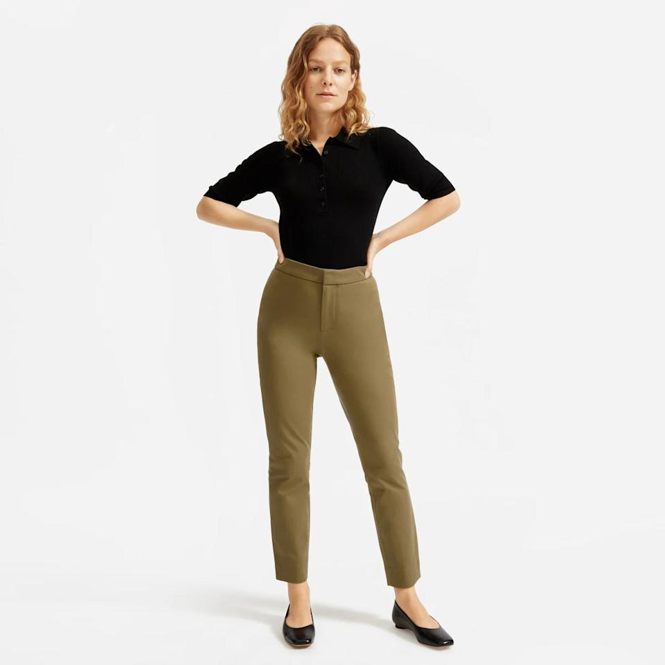 Model wears The Fixed-Waist Stretch Cotton Pant in olive green with a black collared shirt. Image via Everlane.