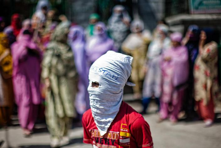 <p>A Kashmiri Muslim masked protester stands in front the women protesters shouting anti Indian and pro Kashmir Independence slogans during a protest, following weeks of violence that has left over 50 people dead and thousands injured, on July 28, 2016 in Srinagar, the summer capital of Indian administered Kashmir, India. (Photo: Yawar Nazir/Getty Images)</p>