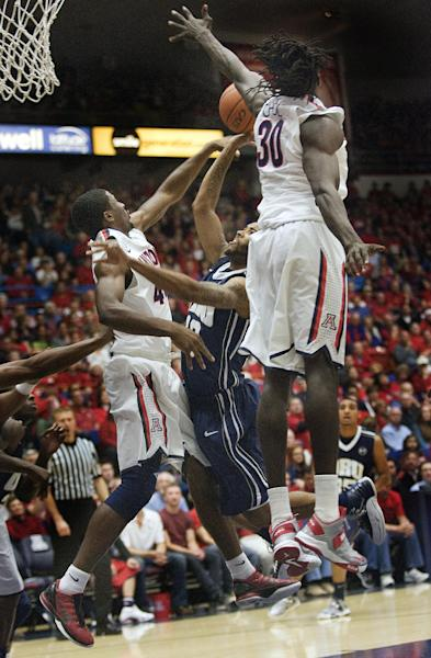 Oral Roberts' Warren Niles (13) tries to shoot over the defense of Arizona's Solomon Hill (44) and Angelo Chol (30) during the first half of an NCAA college basketball game at McKale Center in Tucson, Ariz., Tuesday, Dec. 18, 2012. (AP Photo/Wily Low)
